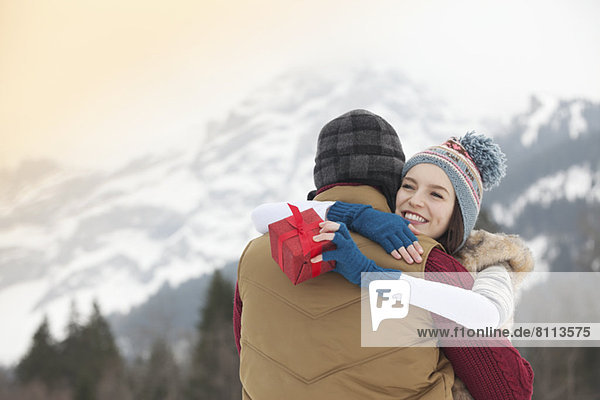 Happy woman holding gift and hugging man with mountains in background