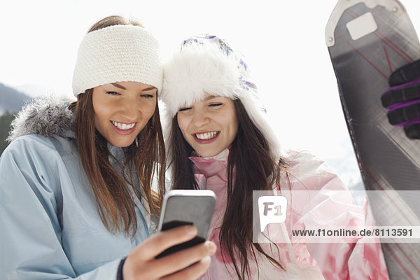Women with skis text messaging with cell phone