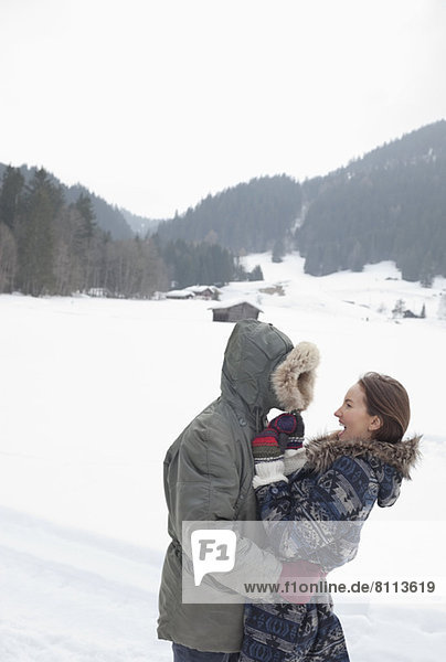 Happy couple hugging in snowy field