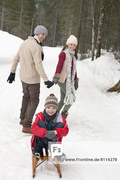 Eltern ziehen fröhlichen Jungen auf Schlitten in verschneiten Wäldern