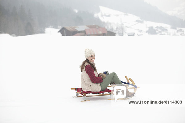 Porträt einer lächelnden Frau beim Rodeln im Schneefeld