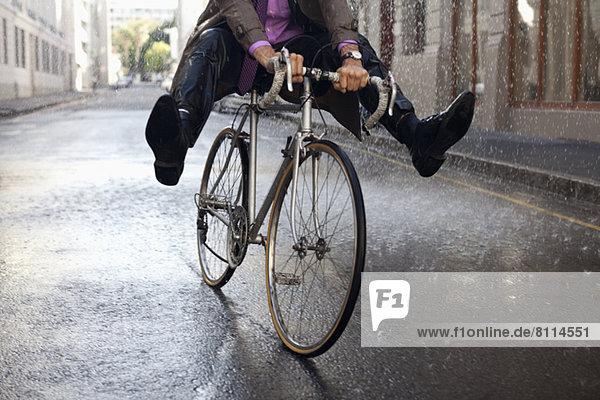 Geschäftsmann Fahrrad fahren mit Füßen im Regen