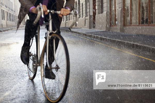 Geschäftsmann auf dem Fahrrad in der verregneten Straße