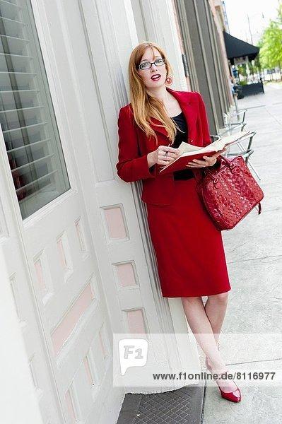 Städtisches Motiv  Städtische Motive  Straßenszene  Straßenszene  Frau  Buch  Umwelt  halten  Gesetz  rot  Anzug  Taschenbuch  Business  alt  Jahr