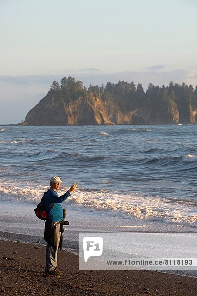 USA  WASHINGTON STATE  OLYMPIC PENINSULA  OLYMPIC NATIONAL PARK  NEAR LA PUSH  RIALTO BEACH  MAN TALKING PHOTO WITH CELL PHONE.