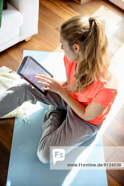 Junge Frau beim Sitzen auf dem Boden mit digitalem Tablett