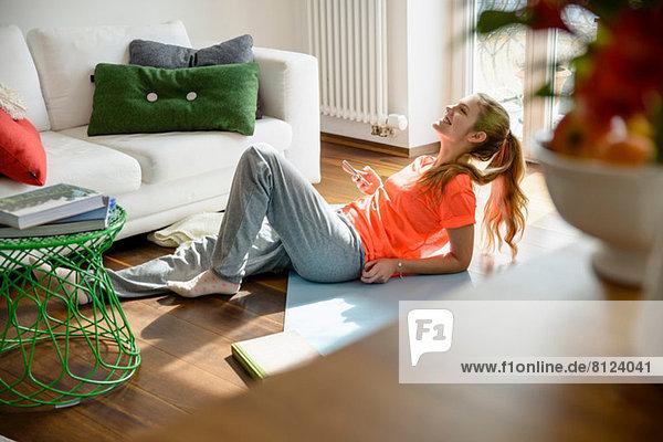 Junge Frau hält Smartphone während sie auf dem Boden liegt