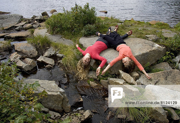 two girls sisters hiking nature forest beauty wilderness lying rocks playing friendship horizontal outdoors daytime color image photography