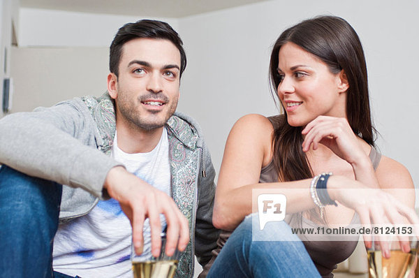 Young couple sitting down sharing glass of wine