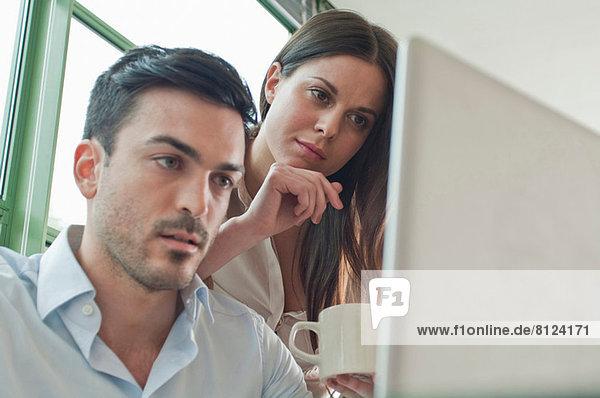 Junge Büroangestellte schauen auf den Laptop