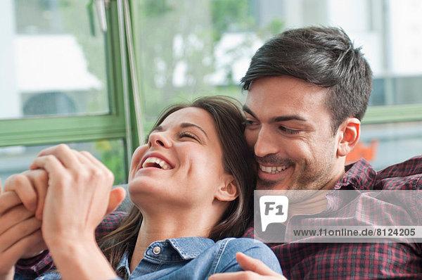 Romantisches junges Paar lacht auf dem Sofa