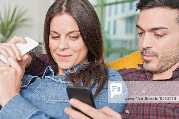 Junges Paar zu Hause mit Mobiltelefonen