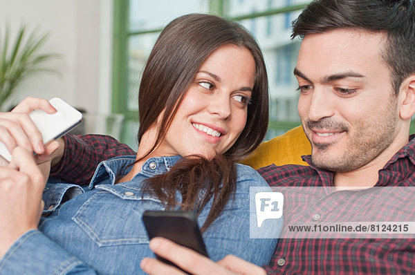 Junges Paar zu Hause mit dem Handy