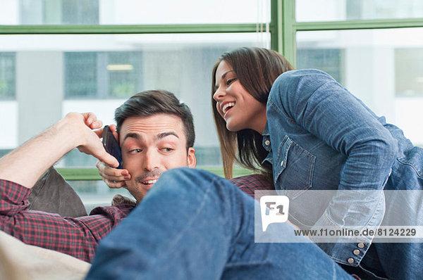Junges Paar zu Hause  das sich mit dem Handy herumtreibt