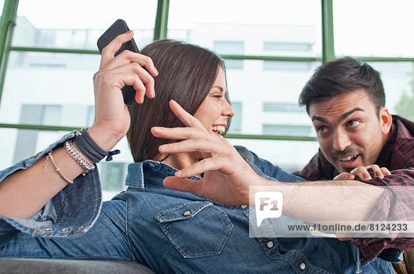 Junges Paar zu Hause  das mit dem Handy herumalbert