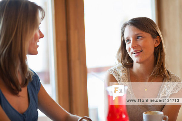 Two young women chatting in cafe bar