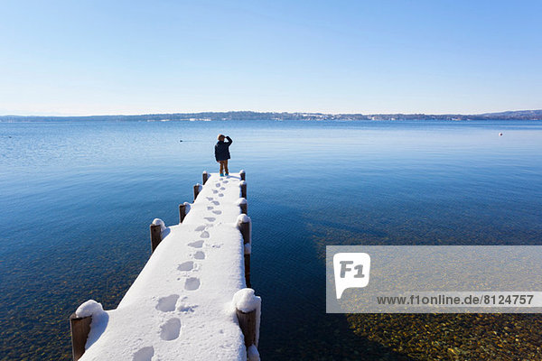 Junge auf schneebedecktem Pier  Starnberger See  Bayern  Deutschland