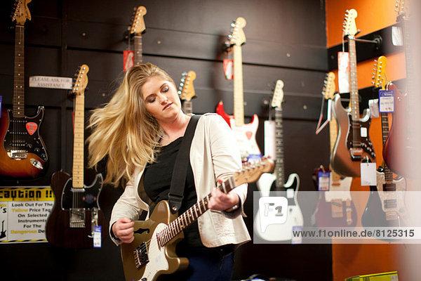 Junge Frau testet Gitarre im Musikladen