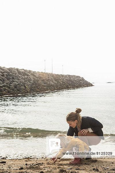 Mutter und Kleinkind bei der Erkundung der Küste