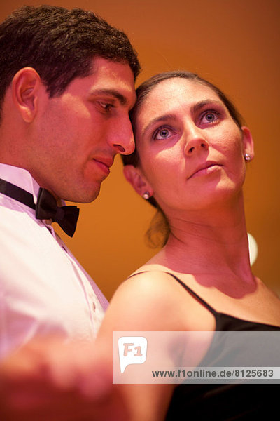 Mid adult woman and young man posing in dance class  close up