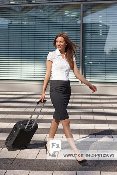 Junge Geschäftsfrau geht mit Trolleygepäck über Fußgängerüberweg