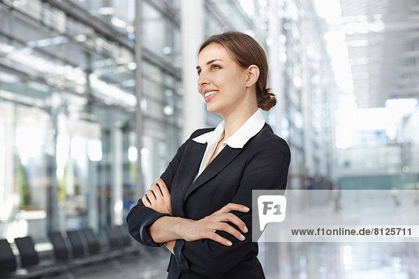 Junge Geschäftsfrau in der Lobby stehend  lächelnd