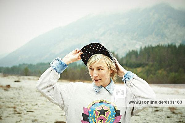 Woman putting cap headwear on