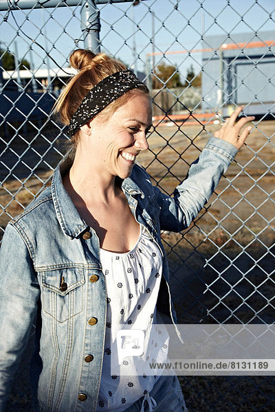 Woman holding fence and smiling