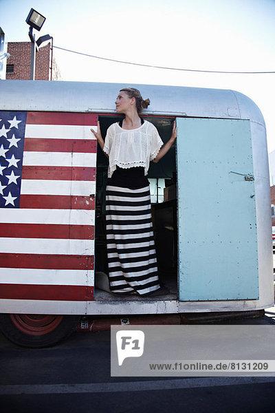 Woman standing in doorway of caravan with American flag