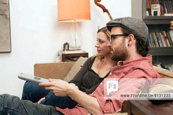 Paar sitzt auf dem Sofa und schaut fern.