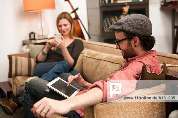 Paar auf dem Sofa sitzend mit digitalem Tablett und Smartphone