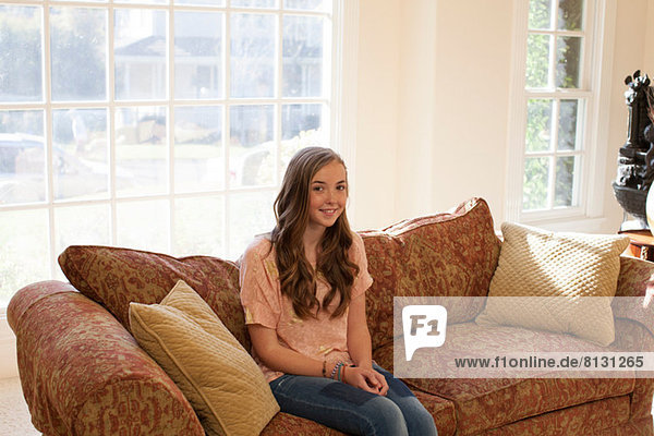 Teenage girl sitting on sofa  smiling