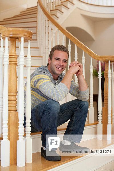 Junger Mann auf der Treppe sitzend
