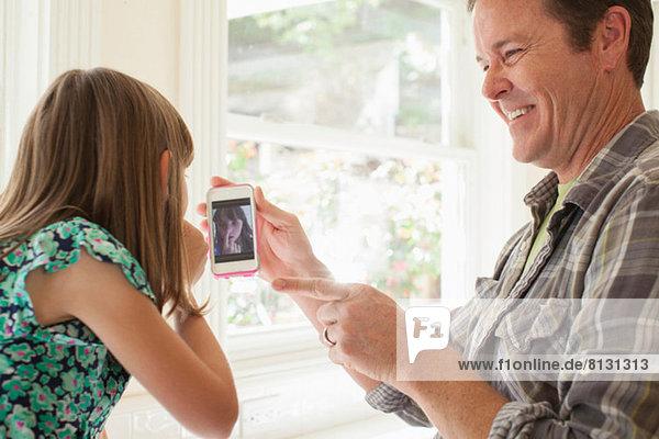 Vater zeigt Tochterfoto von ihr auf dem Smartphone
