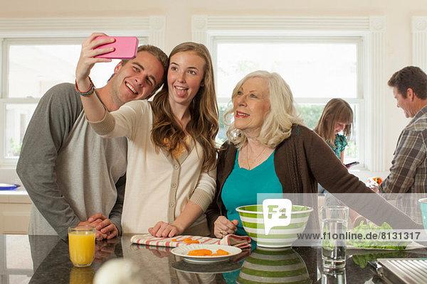Enkelkinder mit Großmutter beim Selbstfotografieren