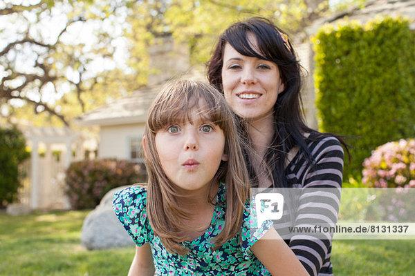 Porträt von Mutter und Tochter  die im Garten das Gesicht ziehen