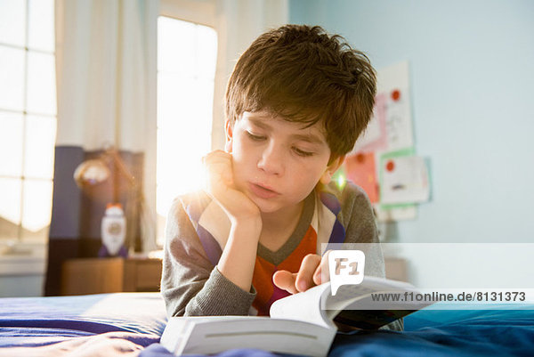 Boy lying on bed reading book