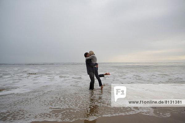 Ein reifes Paar  das sich am Strand umarmt.