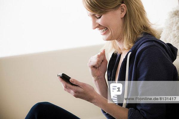Aufgeregte junge Frau mit Handy