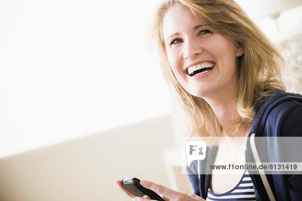 Junge Frau mit Handy  lachend