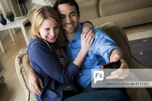 Junges Paar fotografiert sich selbst am Handy