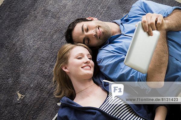 Junges Paar auf dem Boden liegend mit elektronischem Buch