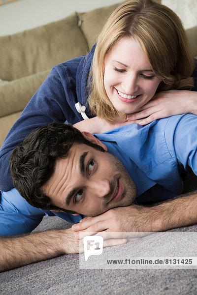 Junges Paar auf dem Boden liegend  Frau auf dem Mann