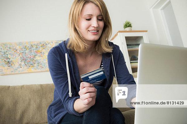 Junge Frau beim Online-Shopping mit Kreditkarte