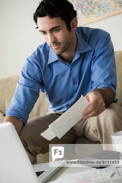 Junger Mann bezahlt Rechnungen online