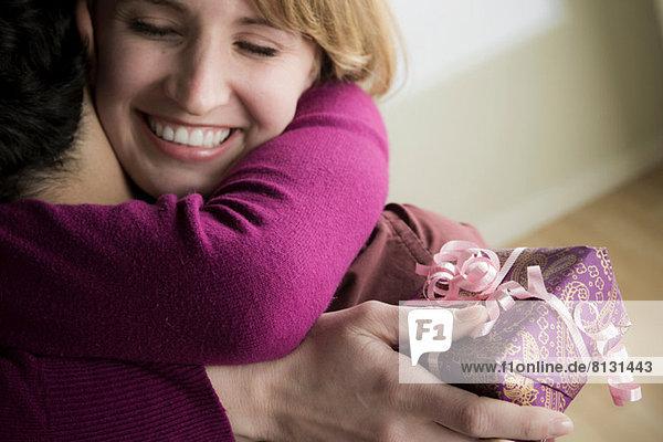 Junges Paar umarmt sich  Frau hält Geschenk