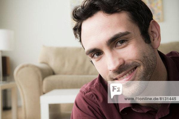 Porträt eines jungen Mannes mit schwarzen Haaren  lächelnd