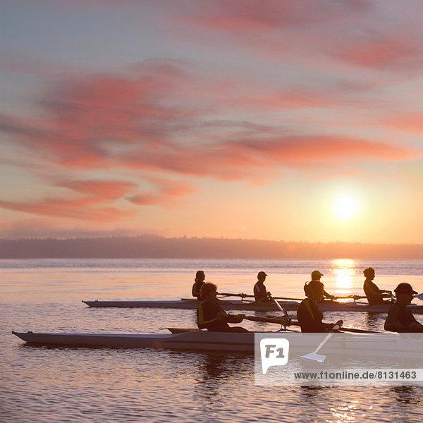 Sieben Menschen rudern bei Sonnenuntergang