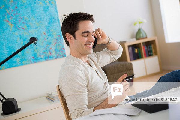 Mid Erwachsene Mann auf dem Handy im Home-Office