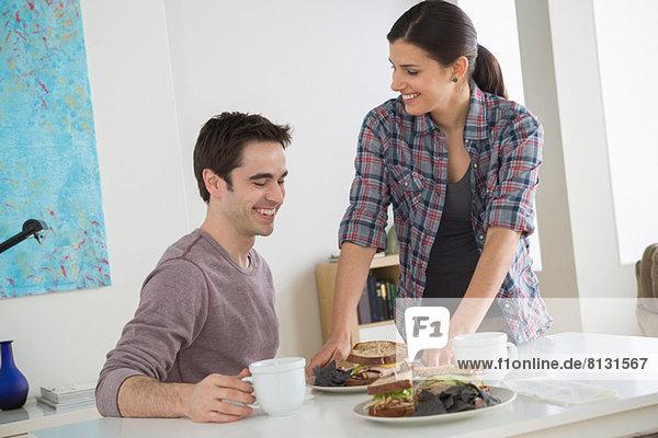 Paar bei Tisch mit Sandwiches